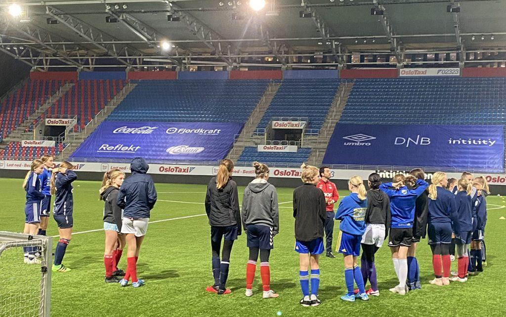 Bildet av jentespillere fra Hasle-Løren og andre samarbeidsklubber på trening på Intility Arena.
